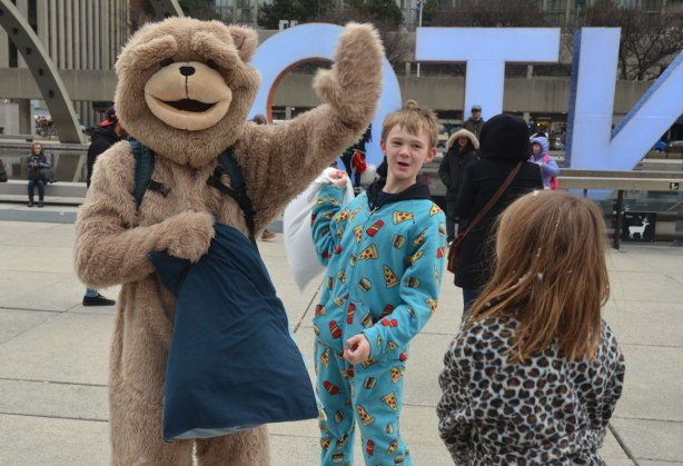 a person in a bear costume waves to the camera as a boy in pyjamas holds a pillow