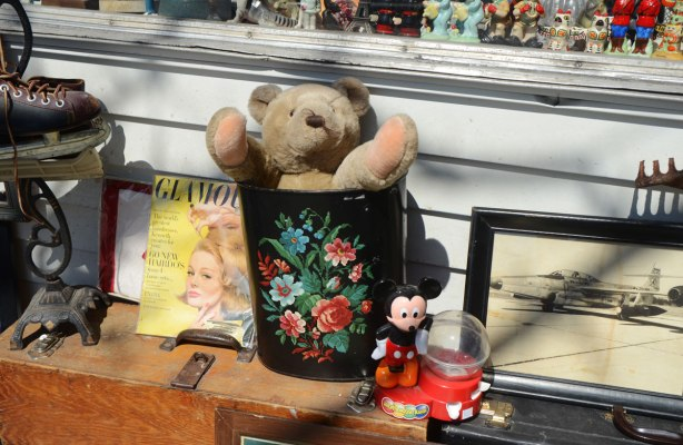 a teddybear sites in a can with a painting of flowers on it. An old Glamour magazine with a yellow cover