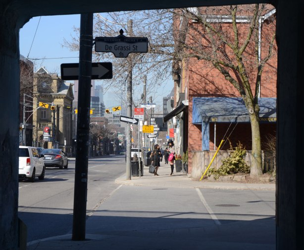 Photo taken from under a bridge, looking west along Queen St. East, cars on the street, a restaurant on the corner, and some women on the sidewalk.