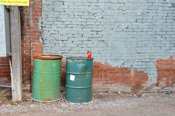 an empty paper coffee cup from Tim Hortons that has been discarded - on top of a dark green barrel that is beside a lighter green barrel, in front of a red brick wall that has been partially painted grey