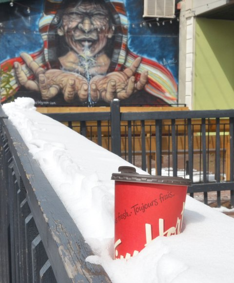 an empty paper coffee cup from Tim Hortons that has been discarded - in the snow on top of a grey wood railing in front of a store. A street art painting of a man with outstretched hands is in the background.