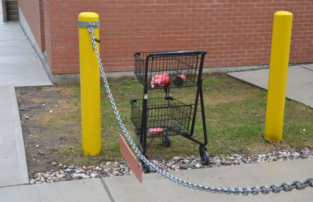 a stolen shopping cart, black metal, sits on a piece of grass, beside the sidewalk, but behind a chained off driveway. In the top part of the cart are 4 TIm Hortons cups and in the bottom part, an empty coke can.
