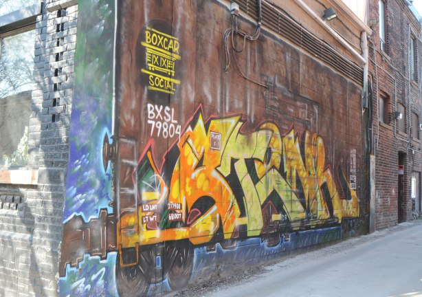 Street art painting of a brown train boxcar, with a yellow and orange tag on it, on the side of a building in an alley.