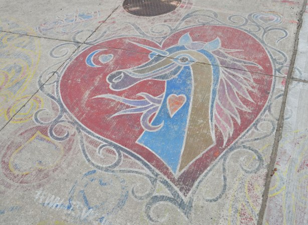 A blue and gold unicorn head painted in a red heart on a sidewalk, by Victor of What's victor up to.
