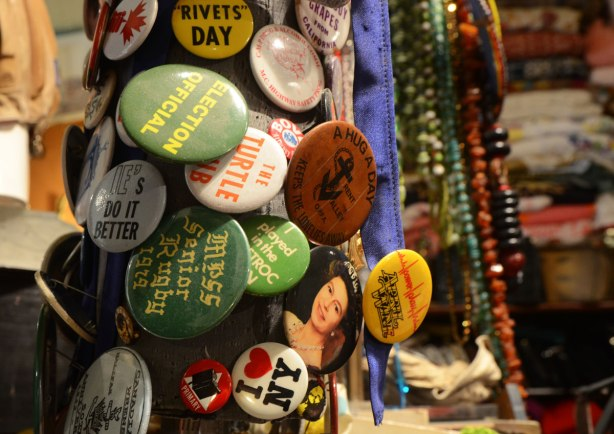 Old pins (buttons) in the foreground with beaded necklaces in the background.