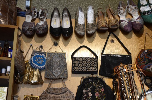 items in a vintage store on Queen St East in Toronto, on the wall there are some small handbags, as well as some high heeled shoes. Some of the bags are beaded and one is a shiny gold colour.
