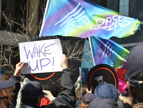 "man holding up a sign that says ""Wake Up"" at a rally protesting for a $15 minimum wage"