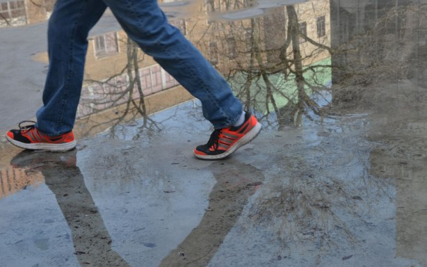 A man's legs as he walks across the pond on Ryerson campus. Very little water is therem lots of reflections of the trees and buildings around. He is wearing jeans and bright orange running shoes.