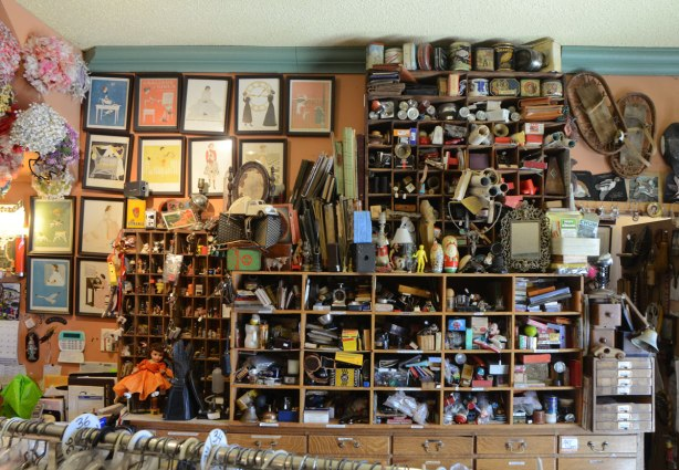 Against a wall in Gadabout store, shelves with small cubbyholes all filled with small items, curios, b=vintage, treasures, such as old producs, toys, figurines, household items,