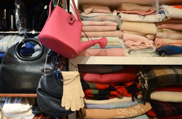 a pink purse in the shape of a watering can hangs from a hook on a wall. A pair of beige gloves hangs below it. Folded fabric items are on the shelves beside the bag and gloves. Blankets or sweaters.