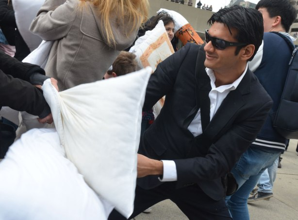 people in the midst of a large pillow fight at Nathan Phillips square in celebration of international pillow fight day - a man wearing a suit and dark sunglasses participates in the pillow fight