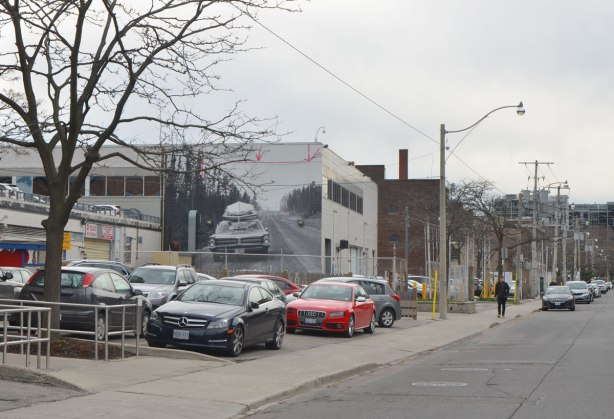 looking down the street past parked cars. A large black and white photo is on the side of the building.