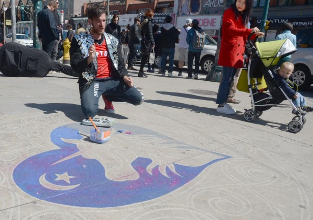 A man is painting a glittery pink and purple unicorn picture on the sidewalk as people pass by on Queen Street in Toronto
