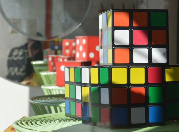 Rubiks cubes and large red and white dice in a store window, some real and some reflected in a a mirror on the wall.