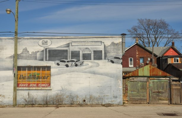 mural on the side of West York motors on St. Clair West near Osler - south end of the mural showing cars parked in front of a garagethe backs of two houses are also in the picture,