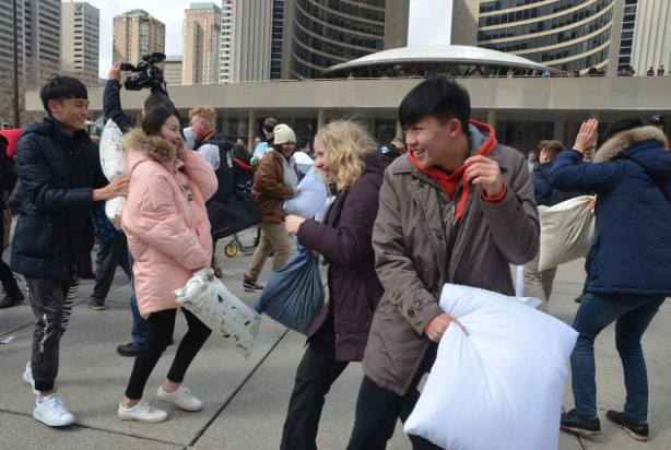 people in the midst of a large pillow fight at Nathan Phillips square in celebration of international pillow fight day - a number of young people laughing