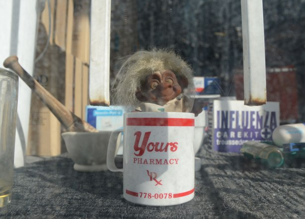 looking into the window of a pharmacy, a toy troll is in a white mug. The mug has red lettering - Yours pharmacy. Also a mortar and pestle in the window along with a box with medicines for influenza