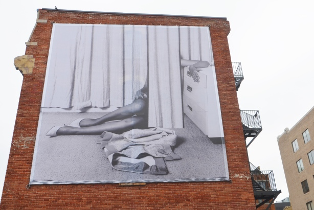 large black and white photo by Eva Strenram called 'Drape'. It is mounted on the upper level of a three storey red brick building. It shows a woman sitting on the floor partially obscured by drapery. Her upper body and head can not be seen.