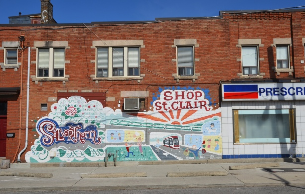 """Silverthorn Sunrise mural by the Davenport Arts Community, with the word Silverthorn, a sun rising over a bridge while a new TTC streetcar passes under the bridge, the words """"shop St. Clair"""". The mural is on the side of a red brick building, beside a pharmacy."""