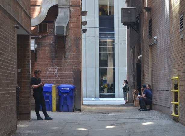 people sitting and standing in an alley, one man is on his cellphone, tall buildings on either side of the lane as well as at the end of the lane