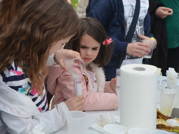 Two young girls are performing an science experiment using beakers and a graduated cylinder. One of them is pouring liquid into the cylinder while the younger one watches.