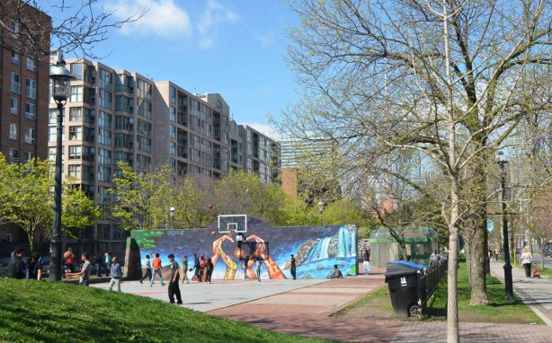 kids playing basketball on an outdoor court. The wall behind the basketball hoop has been painted with a mural of hands making a heart shape with the fingers, by Bruno Smokey and Shalak Attack.
