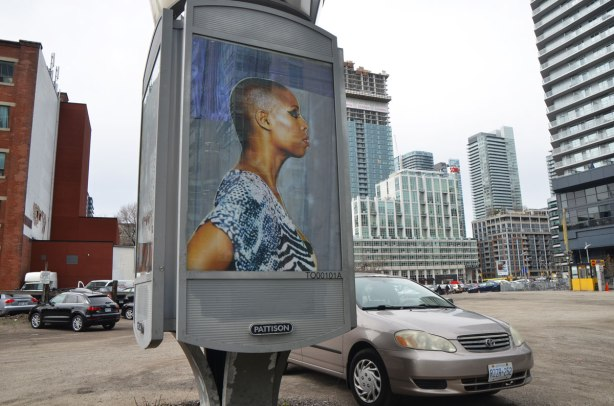 part of an art installation, portrait of a black woman in profile, with a shaved head, on a billboard, by Mickalene Thomas, in a parking lot in downtown Toronto