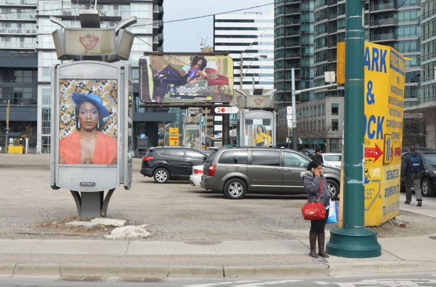 part of an art installation, portrait of a black woman wearing a blue hat on a billboard, by Mickalene Thomas, in a parking lot in downtown Toronto. A woman stands on the corner talking on her phone. Another, large, billboard is in the background.
