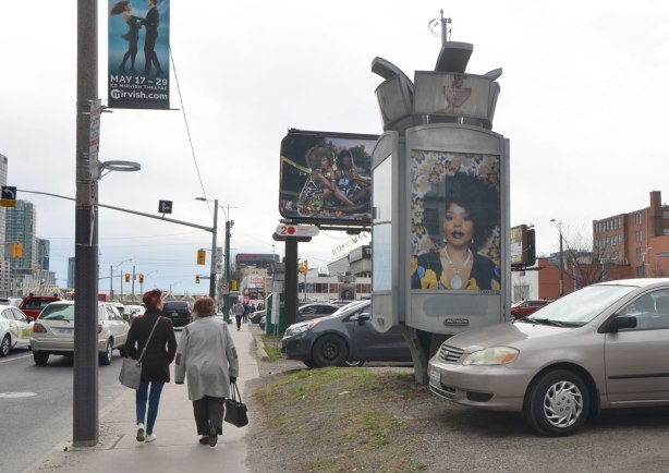 Two women walk past part of an art installation, portrait of a black woman on a billboard, by Mickalene Thomas, in a parking lot in downtown Toronto