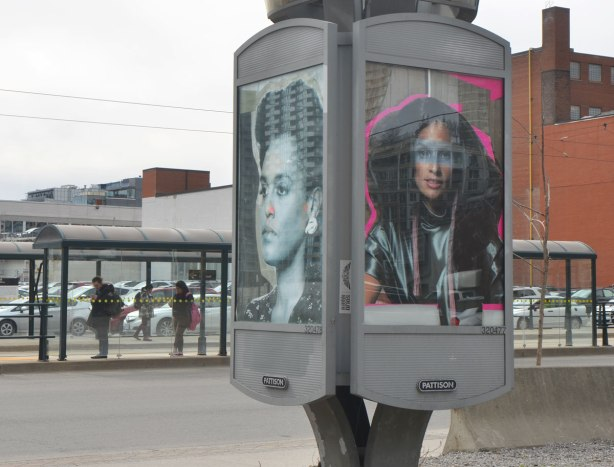 Two portraits of black women, in a billboard space in a parking lot, with people waiting for a streetcar in glass bus shelters in the background.