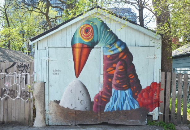 street art mural on a garage door in an alley by birdo - a large bird with blue head and orange beak sitting in a nest looking down at a large white egg