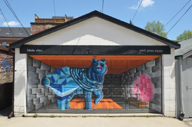 street art mural on a garage door in an alley by birdo - a blue dog beside a pink lava lamp on a table. words: birdo dmc, phil pans tense