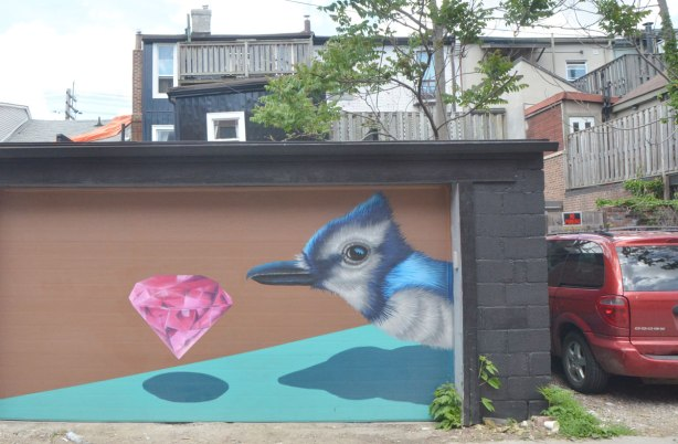 a garage decorated with a mural by birdo, of a realistic blue jay and a pink cut gem floating in front of the bird.