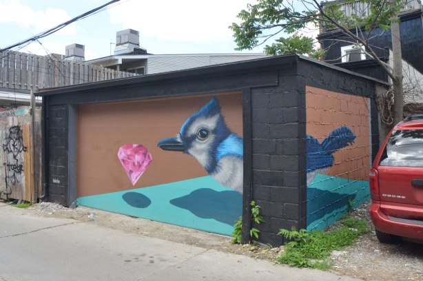 a garage decorated with a mural by birdo, of a realistic blue jay and a pink cut gem floating in front of the bird. The front part of the bird is on the garage door and the back part of the bird is on the side wall.