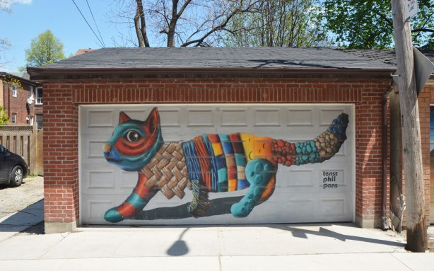 street art mural on a garage door in an alley by birdo - a large multicoloured cat. words: tense phil pans