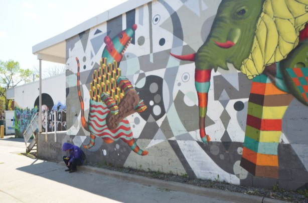 a person is sitting on a kerb in an alley, beside a wall with a large mural by birdo of an elephant and a mouse