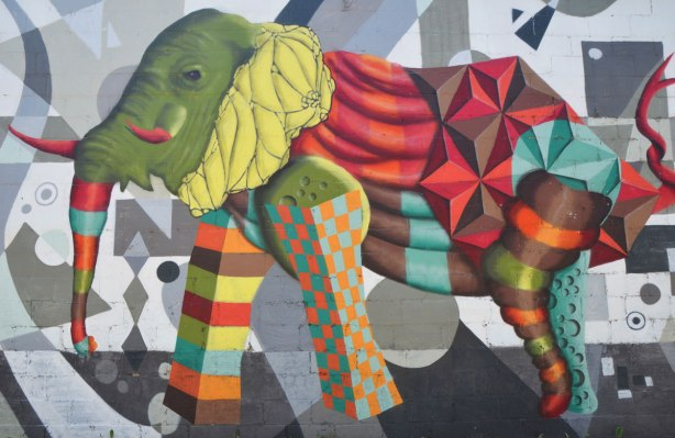 street art mural on a wall in an alley by birdo - an elephant with a green head