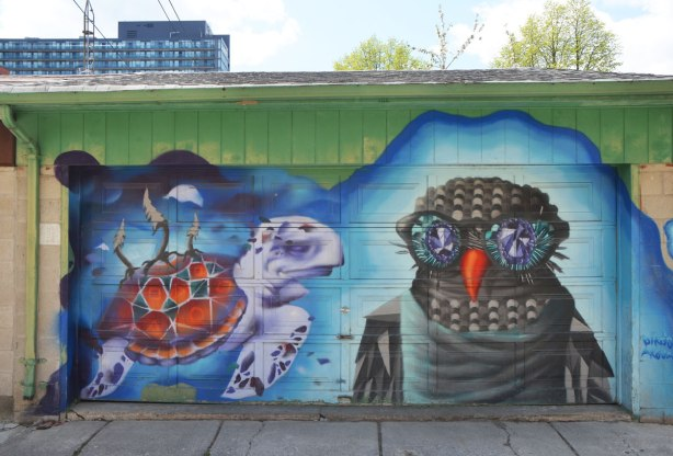 street art mural on a garage door in an alley by birdo - a lavendar turtle and an owl with blue eyes and orange beak