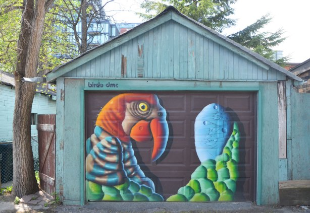 street art mural on a garage door in an alley by birdo - a parrot holding a large blue egg