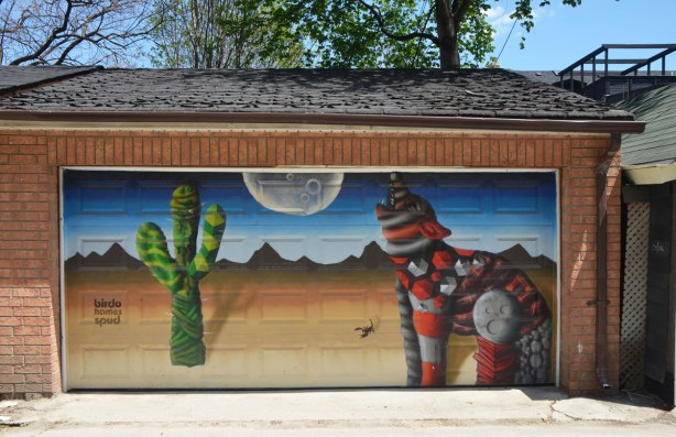 street art mural on a garage door in an alley by birdo - a coyote howling at the moon in the desert with a large cactus in the picture as well as a scorpion. words: birdo homes spud
