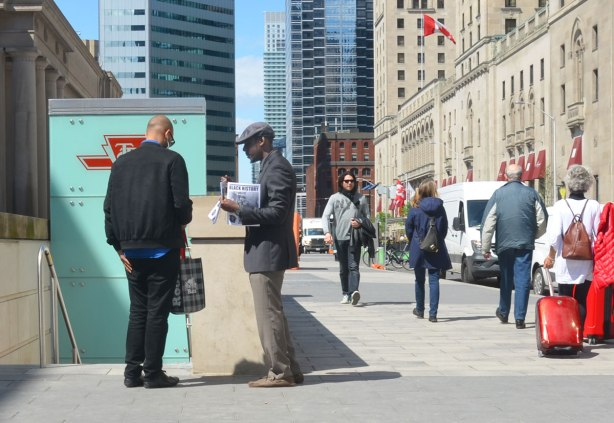 A man is selling Black History newspaper to another man in front of the TTC subwayentrance at Union station.