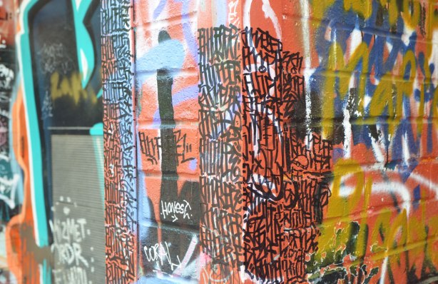 a painted piece of street art has been partially covered with many vertical lines in black marker, producing an interesting pattern over the colours below.