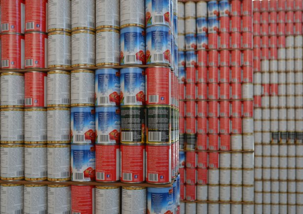 part of a large 3D design made of canned food in white, blue and pink with a few black details.