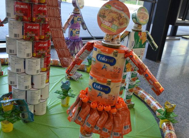 models of children made with packaged food. A girl is made with orange enfamil containers, bowl of noodles for head, tubes with orange packaging as a skirt, and cyclindrical packages of cookies as arms