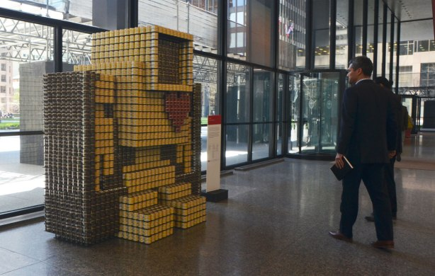A large 3D lovebot, about 6 feet tall, made of canned food stands in the lobby of the TD centre, it's an entry in the Canstruction event. Two men in suits are looking at it.