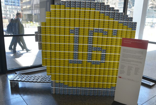a large measuring tape (round and yellow) made of tin cans full of food to be donated.