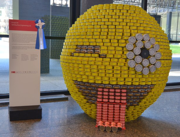 made of canned food, a large yellow circle meant to look like an emoji, winking with it's tongue out. It's about 5 feet high.