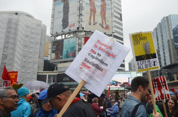 "A man holds a placard that says ""Enough is enough, No to Capitalism, Socialism now""May day, International Workers Day rally at Dundas Square on a rainy day -"