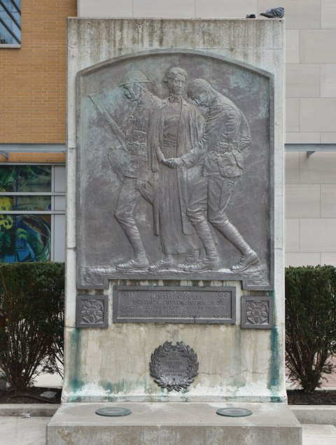 A memorial to British nurse Edith Clavell and the Canadian nurses of WW1, a bronze plaque mounted on a stone tablet. Picture of Clavell between two upright but wounded soldiers.