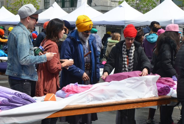 People having their heads wrapped in a turban, many different colours, at an event at Yonge Dundas square run by the Sikh Youth Federation. Sikh volunteers are making the turbans using stacks of fabric laid out on 5 long tables. Choosing magenta fabric
